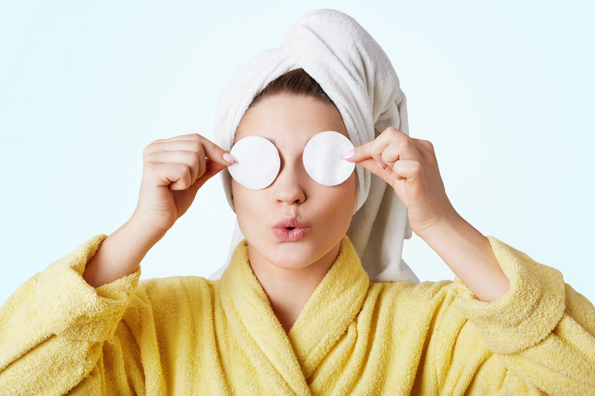 Funny woman foolishes after taking shower, wears towel and bathrobe, covers eyes with cotton wheels, going to apply cosmtics and do make up, isolated on white background. Beauty and hygiene concept